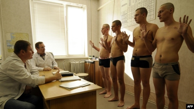 Conscripts shows their palms to a doctor at the military registration and enlistment office in the southern city of Krasnodar