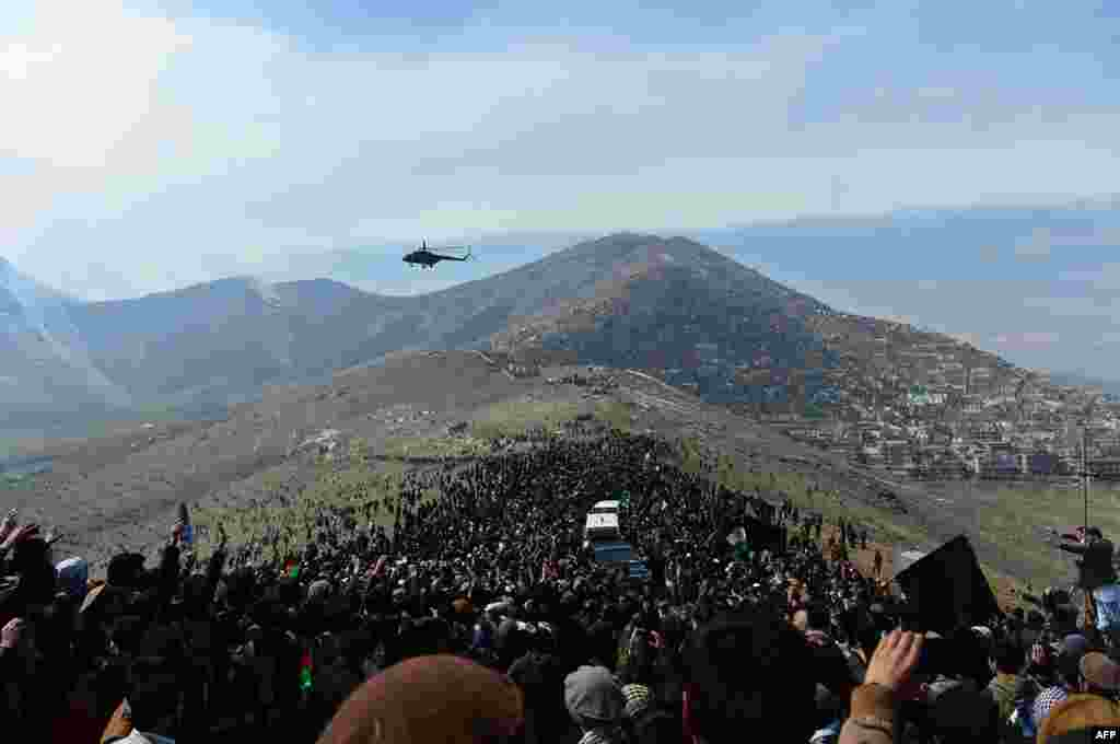 A helicopter flies over Afghan residents as they attend the burial of Vice President Marshal Mohammad Qasim Fahim, formerly one of the country's most feared warlords, at a ceremony on a hilltop in Kabul on March 11. (AFP/Wakil Kohsar)