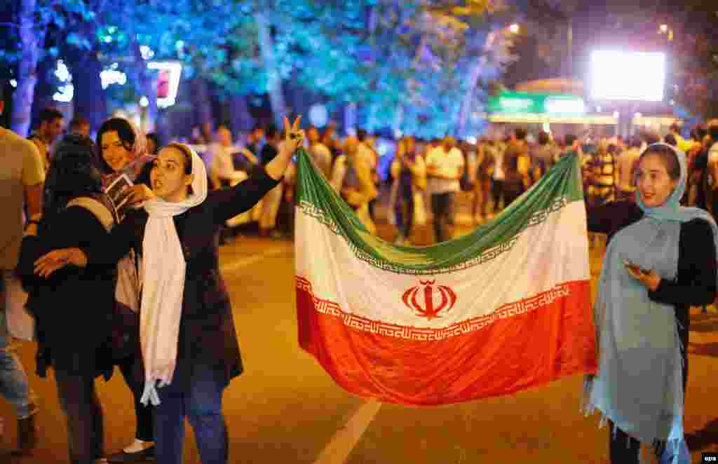 Women carry the Iranian flag.