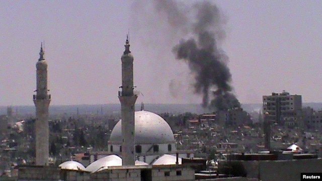 Smoke rises from the Juret al-Shayah district in the Syrian city of Homs on July 11.