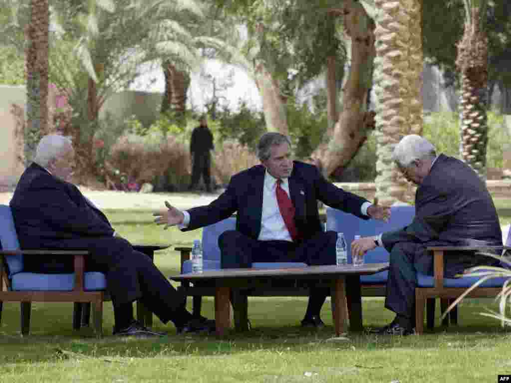 Middle East peace efforts - U.S. President George W. Bush (center) Israeli Prime Minister Ariel Sharon, (left) and Palestinian Prime Minister Mahmud Abbas talk during a meeting on June 4, 2003, in the Jordanian Red Sea resort of Aqaba.