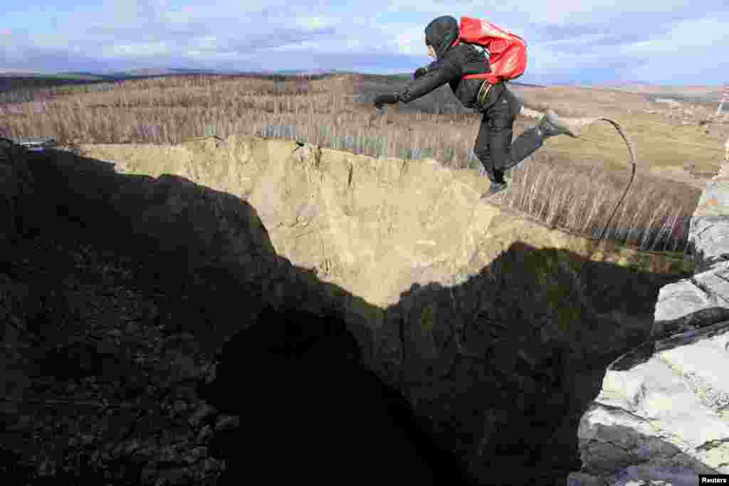 "A member of the ""Exit Point"" amateur rope-jumping group jumps from a 120-meter rock down to a man-made crater called Tuimsky Proval, near the Russian town of Tuim on October 20. (Reuters/Ilya Naymushin)"