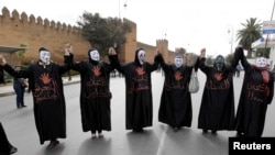 Halkara 8-nji mart baýramçylygynda maska geýip, protest şygarlaryna gygyrýan morokkaly aýallar. Arhiw suraty