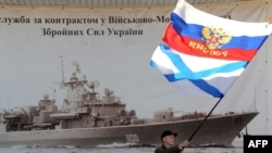 Ukraine -- A man waves a Russian flag and a Russian Navy flag in front of the headquarters of the Ukrainian Navy in Sevastopol on March 3, 2014.
