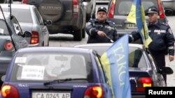 په یوکراین کې د ټرفیک پولیسو یو عسکر د موټرونو د قطار په سمولو بوخت دی