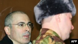 Mikhail Khodorkovsky (left) inside a bullet-proof glass dock in a Moscow court in March 2009