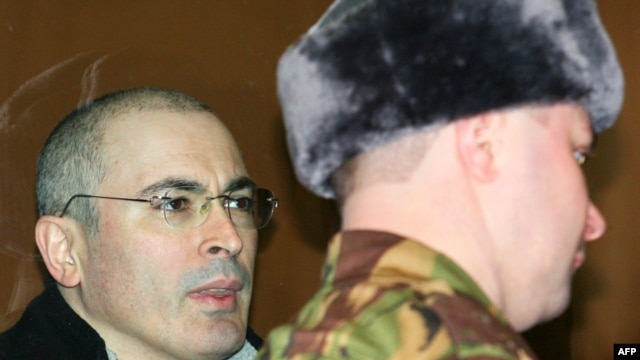 Mikhail Khodorkovsky (left) stands inside the bulletproof glass defendents' cage in a Moscow court on March 3.