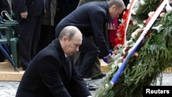 Владимир Путин и Дональд Туск возлагают цветы к мемориалу в Катыни.