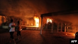 A vehicle and surrounding buildings burn after they were set on fire inside the U.S. Consulate compound in Benghazi, Libya, on September 11.