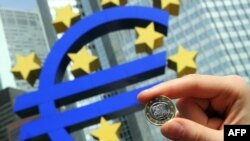 Germany -- A woman poses with a Euro coin in front of the giant symbol of the European Union's currency the Euro in the background outside the headquarters of the European Central Bank in Frankfurt, 29Apr2010