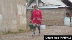 Женщина несет воду. Шымкент, 14 октября 2015 года.