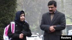 Malala Yousafzai walks with her father Ziauddin as she attends the Edgbaston High School for Girls in Birmingham in March.