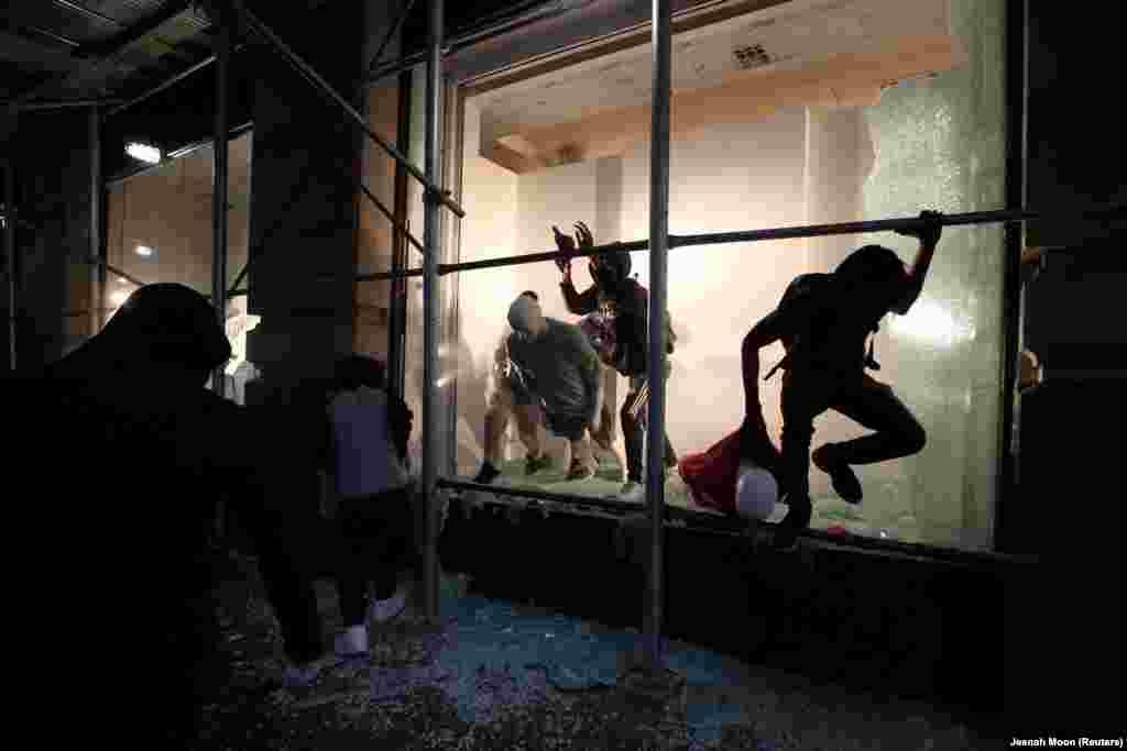 Чоловік вистрибує з магазину через розбиту вітрину в Нью-Йорку. У місті тривають акції протесту через смерть Джорджа Флойда. Нью-Йорк, 2 травня 2020 року (Фото REUTERS/Jeenah Moon)
