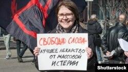 Протестующая с плакатом у здания государственных органов в России (архивное фото)