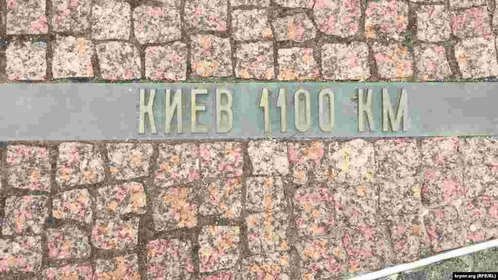 От скульптуры расходятся плиточные «лучи», на которых указано расстояние от Керчи до других городов Украины