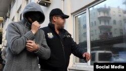 На снимке, сделанном турецким журналистом, – полицейский сопровождает задержанного гражданина России. Адвокаты утверждают, что трое россиян арестованы не после, а накануне теракта в Стамбуле
