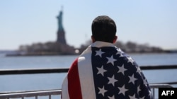 Участник марша иммигрантов смотрит на статую Свободы. Нью-Йорк, 6 апреля 2013 года. Иллюстративное фото.