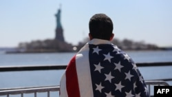 An immigrant looks toward New York's Statue of Liberty during a march for immigration reform in April.