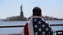 Мужчина с американским флагом на спине смотрит на Статую Свободы в Нью-Йорке.