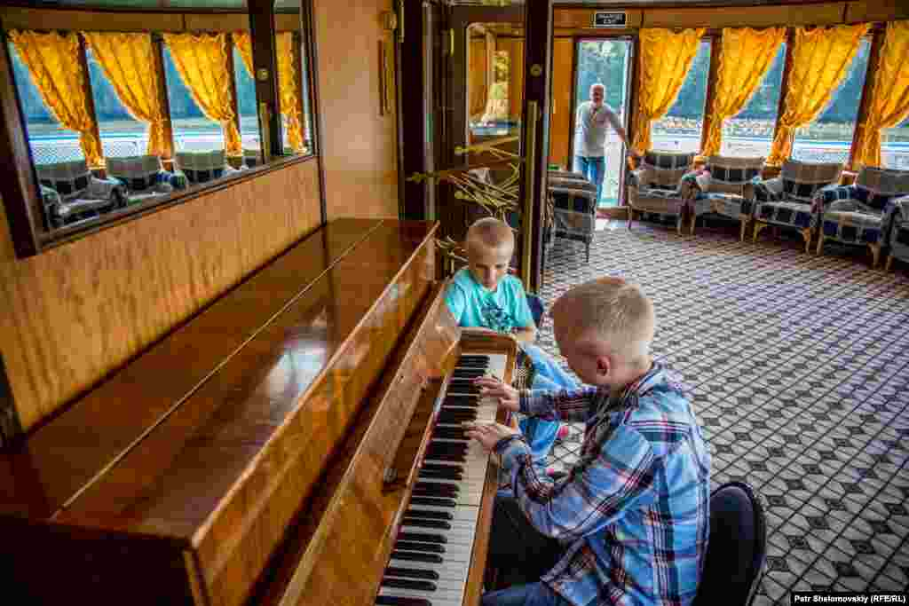 Children play piano on board a boat that has been converted into a hotel.