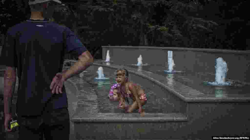 Мужчина собирается чистить фонтан, в котором купаются дети