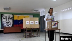 Seçki məntəqəsində Hugo Chavez-in portreti asılıb