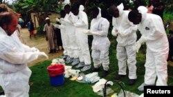 Добровольцы готовятся к погребению человека, скончавшегося от вируса Эбола, Сьерра-Леоне.