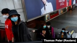 Люди в медицинских масках на эскалаторе в торговом центре в Пекине. 25 марта 2020 года.