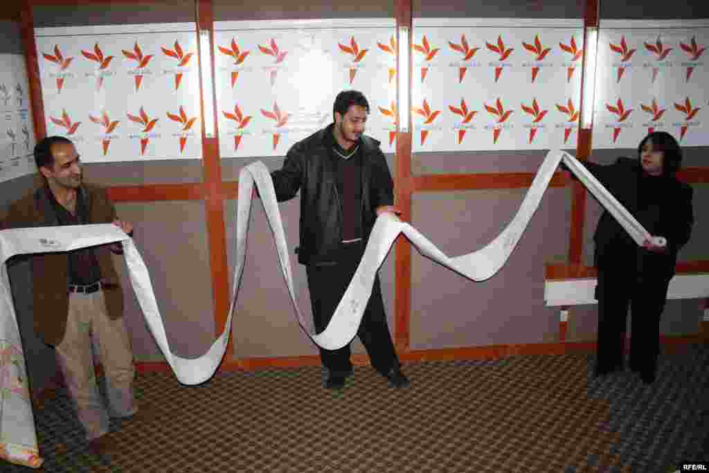 "Radio Azadi employees hold a 40-meter letter from Afghanistan to be displayed at the Library of Congress in Wash-D.C. - RFE exhibit ""Voices From Afghanistan"" displaying some of the thousands of hand-painted scrolls and letters received by Afghanistan's most popular radio station, RFE/RL's Radio Azad held in the Library of Congress in Washington D.C. The exhibit - ""Voices From Afghanistan"" - offered a window into the daily lives of ordinary Afghans from various ethnic communities across all parts of the country."