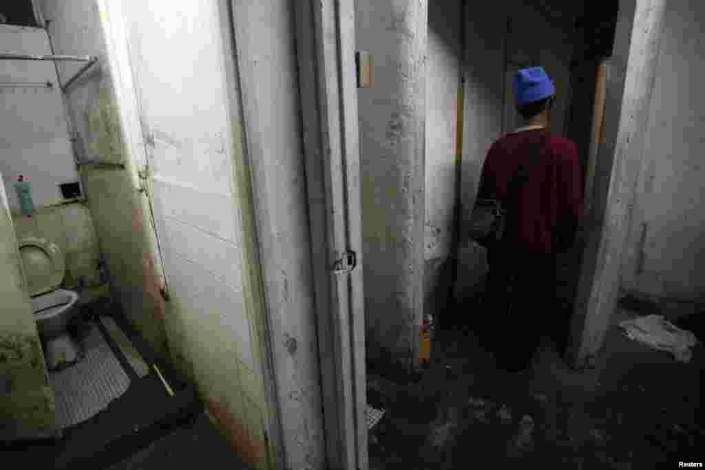 Ng, a 60-year-old man, leaves a communal toilet near his 5.6-square-meter subdivided flat inside an industrial building in Hong Kong. (2012 photo)