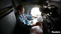A Vietnamese military officer works within a Vietnamese air force AN-26 during a mission to find the missing Malaysia Airlines flight MH370 off Tho Chu islands on March 11.