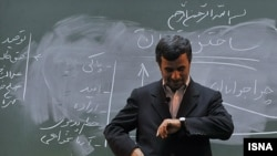 Former Iranian President Mahmud Ahmadinejad looks at his watch in front of the chalkboard in a university lecture hall. (file photo)