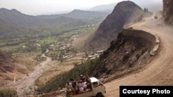 PAKISTAN - Passengers ride along a mountainside road in Pakistan's North West Frontier Province.