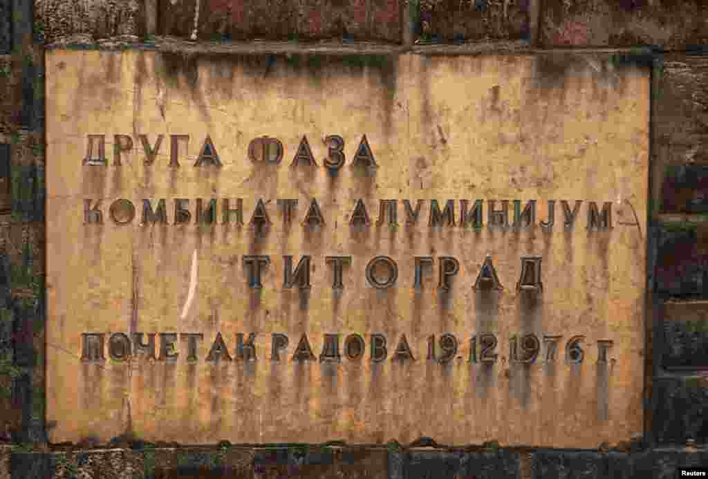 "A plaque reads: ""Second phase, aluminium factory, Titograd [the former name of Podgorica], work started 19.12.1976."""
