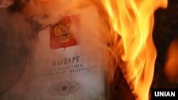 Палаючий паспорт громадянина Росії біля будівлі російського генерального консульства в Одесі під час акції вшанування пам'яті жителів Маріуполя, вбитих в результаті обстрілу російських гібридних сил. Одеса, 25 січня 2015 року