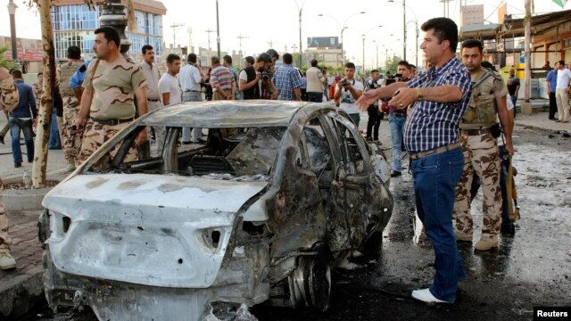 Members of the Kurdish security forces inspect the site of a suicide bombing attack in Kirkuk on June 25.