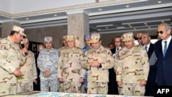 A handout picture released by the Egyptian Presidency on February 25, 2018, shows Egyptian President Abdel Fattah al-Sisi (C) dressed in military uniform during his visit to the headquarters of the eastern forces of the Suez Canal at an unknown location i