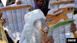 Women read mock ballots produced as part of a voter-education campaign ahead of the presidential and provincial elections in 2009.