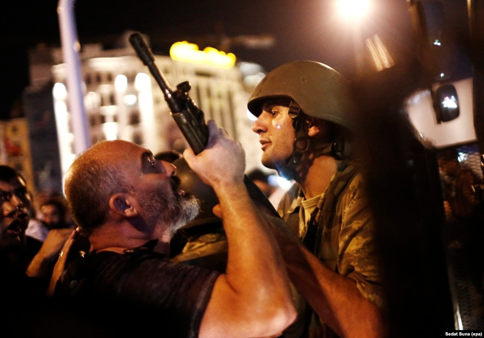 """When I got to Taksim Square, one of the [coup] soldiers asked, 'What happened, why are we here?' I told him: 'This will become dangerous for you, you should go home now.' This photograph was of the last soldier on the square who hadn't been arrested. ""The atmosphere was very angry. The man on the left is a special-forces policeman saying: 'You need to stop this. Give me the gun.' The soldier was saying: 'I'm not giving you my weapon. I have orders, if you try to take it from me I will start shooting.' This argument lasted maybe one minute, then the policeman arrested him.... A lot of the soldiers thought they were in a training exercise. Now they are probably still in prison. It's very sad."" -- Epa photographer Sedat Suna describing the scene he encountered in Istanbul as an attempted coup plunged Turkey into a night of chaos in July."