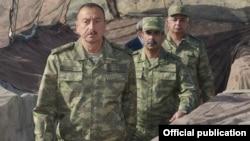 Министр обороны Азербайджана Закир Гасанов (в центре) вместе с президентом страны Ильхамом Алиевым (на переднем плане) на Агдамском участке линии соприкосновения, 6 августа 2014 г․