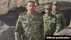 Azerbaijan - President Ilham Aliyev and Defense Minister Zakir Hasanov (C) visit Azerbaijani troops in Agdam district, 6Aug2014.