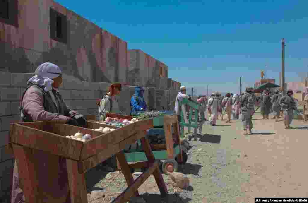 U.S. soldiers from Fort Irwin pose as Afghan street vendors in Medina Jabal, one of two mock towns constructed at the training center to simulate urban combat environments.