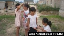 Дочери Айгуль Кенжехан играют с соседской девочкой. Алматинская область, 7 августа 2016 года.
