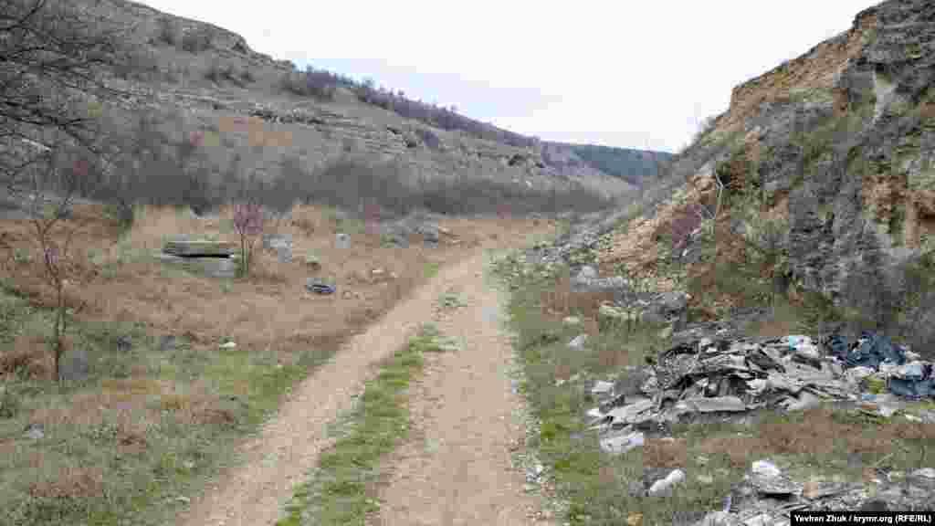На определенном участке балки асфальт заканчивается, дальше идет грунтовая дорога. На склонах – пещеры, которые образовались из-за физического выветривания. Обломки шифера, куски автомобильных запчастей, пластик и просто бытовой мусор стали привычными пейзажами Сарандинакиной балки