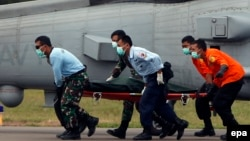 Спасатели переносят тело одного из погибших в авиакатастрофе