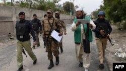 Счетчики переписи населения в Пакистане идут в сопровождении сотрудников сил безопасности. Пешавар, 15 марта 2017 года.