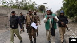 Pakistan -- Pakistani soldiers and policemen guard an official (2nd R) from the Pakistan Bureau of Statistics as they arrive in a residential area to collect information for a census in Peshawar, March 15, 2017