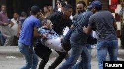Morsiniň tarapdarlary protest mahalynda ýaralanan protestçini göterip barýarlar. Ramses skweri, Kair. 16-njy awgust, 2013.
