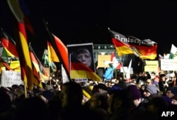 Marchers at the January 12 rally in Dresden, organized by German right-wing populist movement Pegida (Patriotic Europeans Against the Islamization of the Occident), hold up German flags and a doctored image of German Chancellor Angela Merkel.