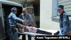 Конвоиры вытаскивают из автомобиля носилки с лежачей больной заключенной Гаухар Худабаевой. Алматинская область, 20 июня 2019 года.